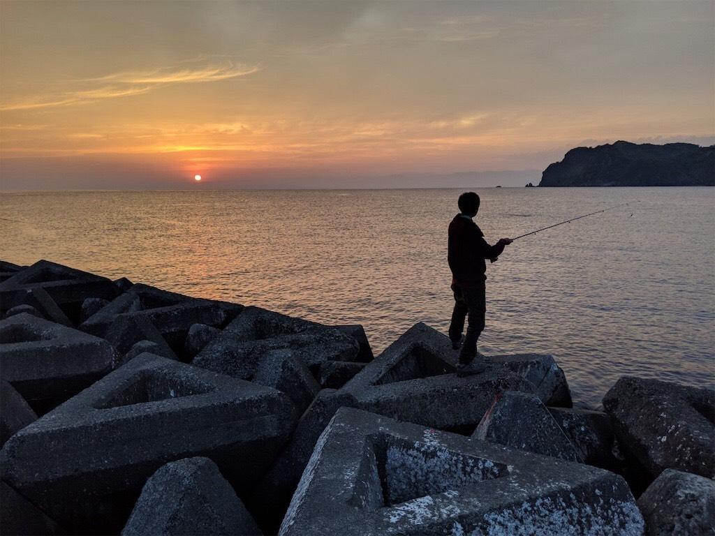 夕暮れ時に釣りをしている人